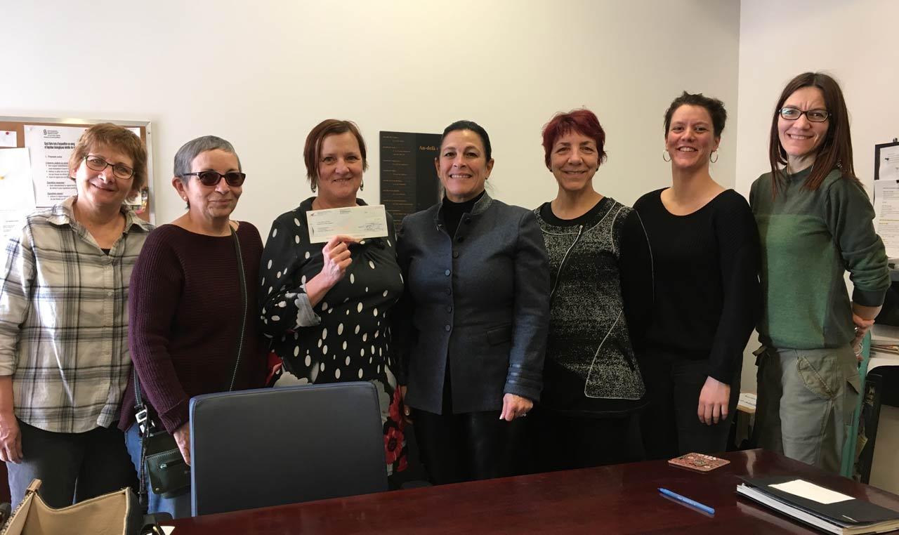 La directrice exécutive du SEPB-Québec, Kateri Lefebvre, en compagnie de Micheline Cyr, directrice de l'Auberge Madeleine, et d'une partie de son équipe. Le SEPB-Québec a fait un don de 2 000 $ en plus de produits d'hygiène personnelle recueillis par les membres lors de de divers événements. Une vidéo est aussi disponible sur la page Facebook du SEPB.